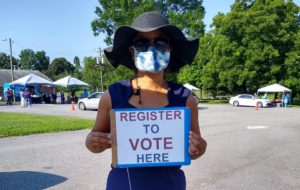 Woman in hat holding Register to Vote sign in parking lot