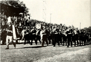 Drum major leads NC A&T Marching Band in front of crowd at Homecoming 1945