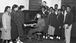 Man at piano surrounded by young people at East White Oak Community Center, 1952